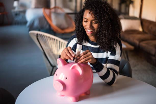 Black woman with saving piggy bank stock photo