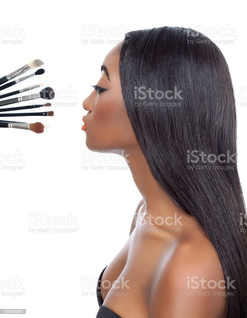 Black woman with straight hair and makeup brushes stock photo