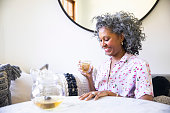 A black woman with a cup of tea at a brightly lit table