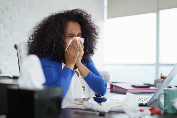 Black Woman Working from Home And Sneezing For Cold stock photo