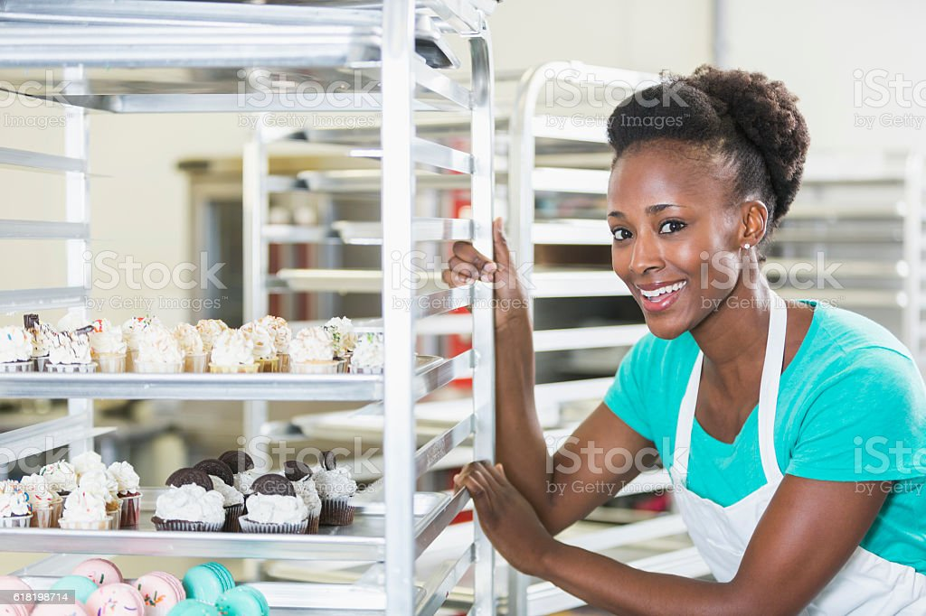 Black woman working in bakery, with trays of baked goods stock photo