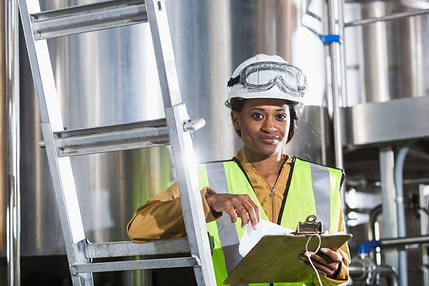 Black woman working in factory with clipboard, hardhat stock photo