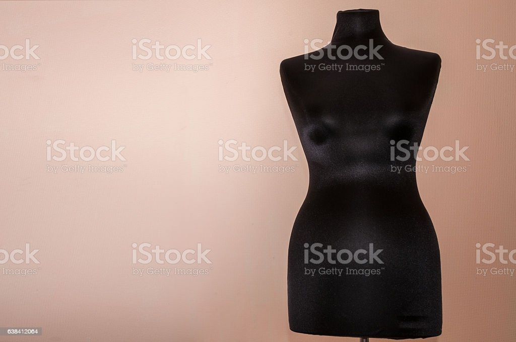 Black women sewing mannequin standing on a beige background stock photo