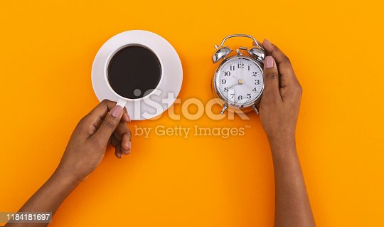 Morning coffee concept. Black female hands holding alarm clock and cup with hot drink over orange background, top view