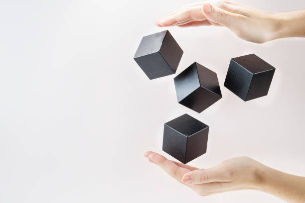 Black wooden cubes are floating on open woman hand.  Concept of creative, logical thinking. Abstract background with cubes with copy space. Shape floating. stock photo