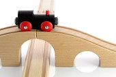 Black wooden toy train on bridge rail isolated on white