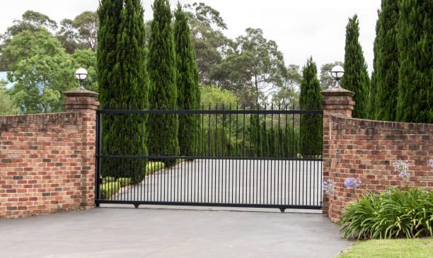 Black wrought iron driveway entrance gates stock photo