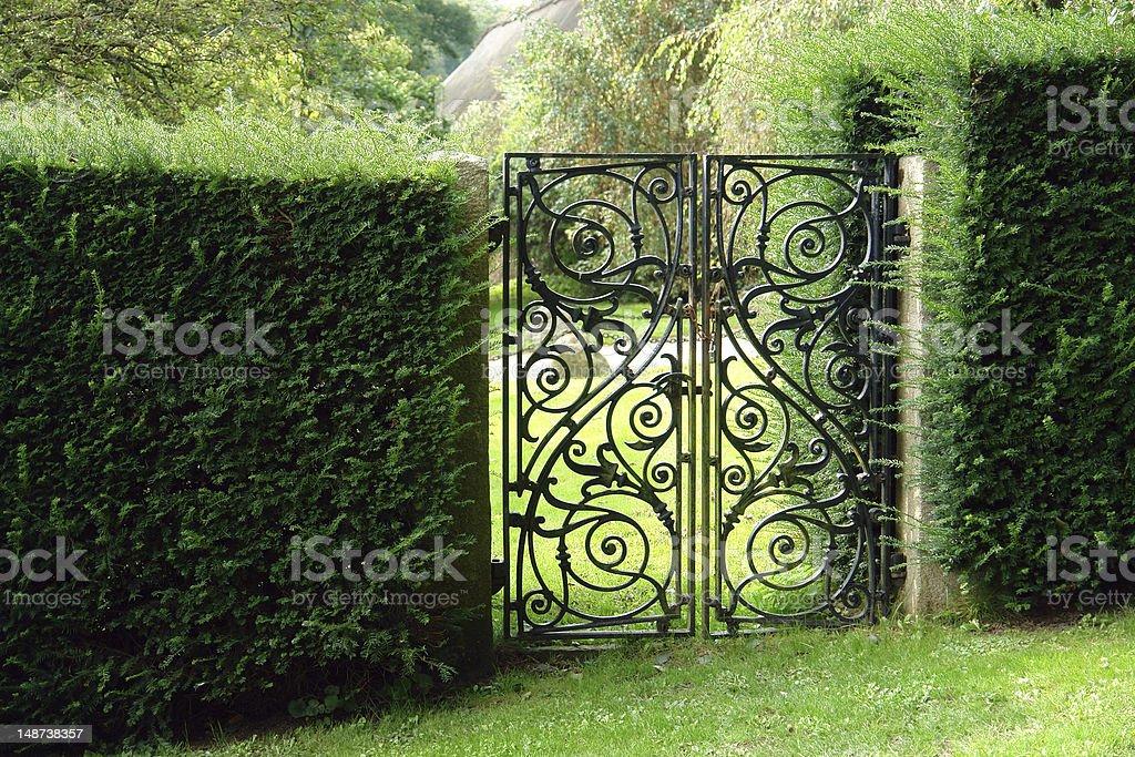 Black wrought iron garden gate stock photo