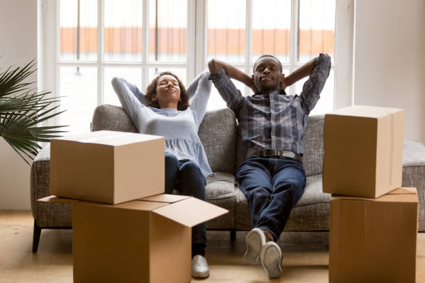 Black young couple relax on couch tired on moving day stock photo