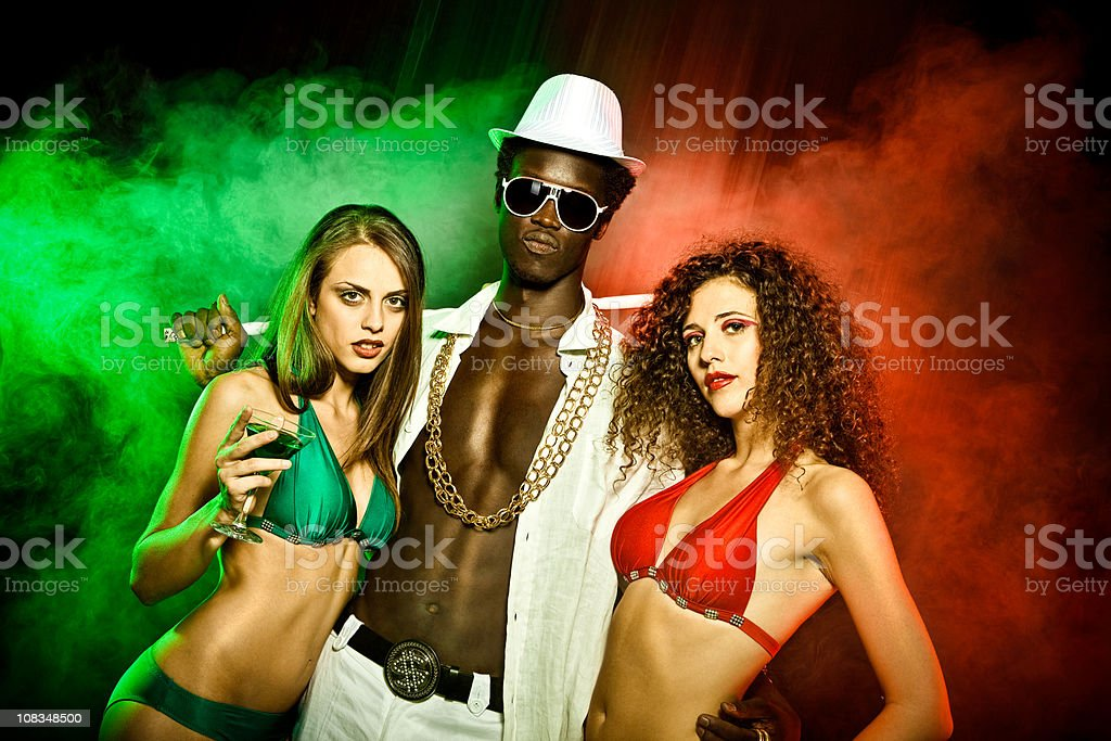 Black young rapper with two girls in bikini red green stock photo