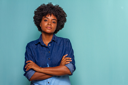 Black woman with curly hair wearing a blue jeans shirt on blue background