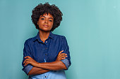 istock Black young woman with black power hair wearing a blue jeans shirt on blue background 1226677905