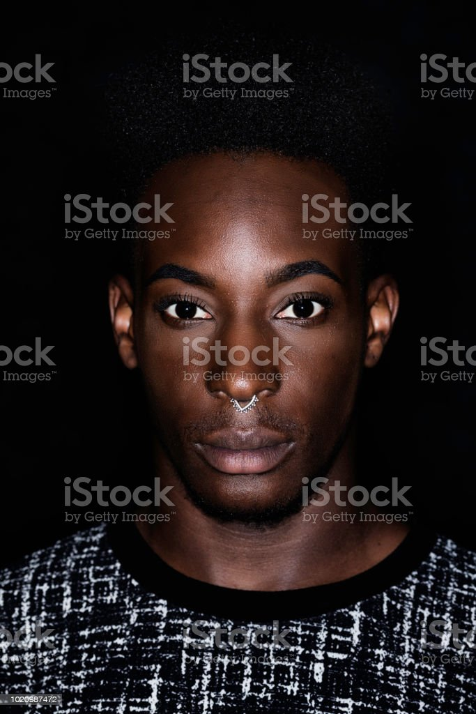 Portrait of a young man of Afro-Caribbean ethnicity wearing a nose...