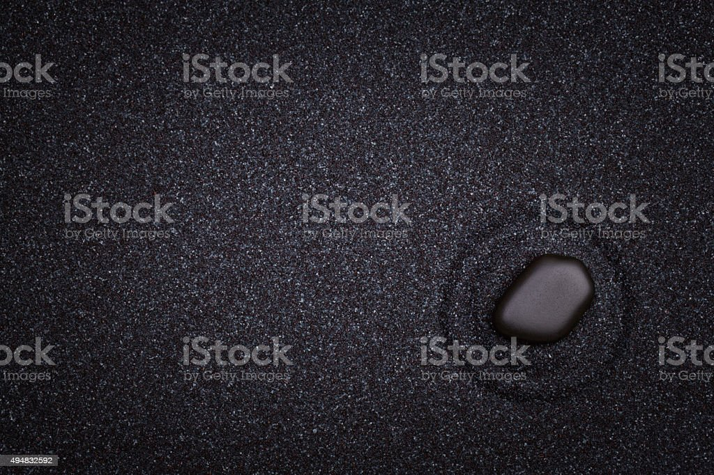 Black  zen stone with circle patterns in the sand stock photo