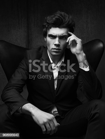 istock Black-and-white business portrait of a serious young man sitting in a chair 968995640