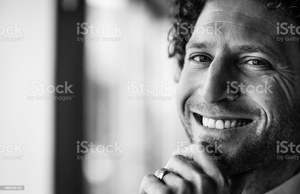 Black-and-white close-up photo of smiling man with stubble stock photo