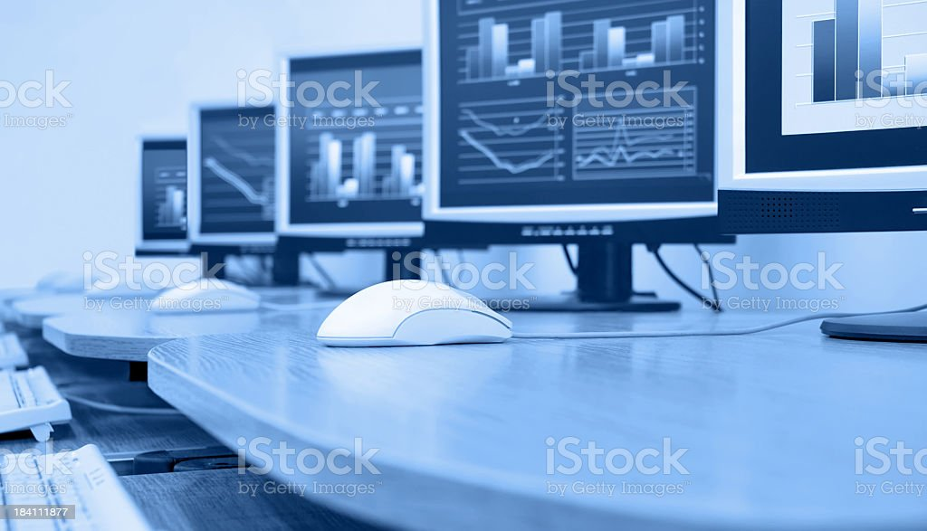 Black-and-white of a row of classroom computers on wood desk stock photo