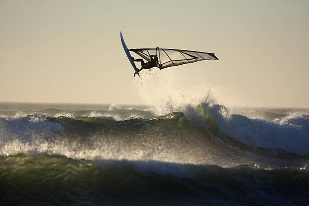 Black-and-white photo of person wind surfing large waves stock photo