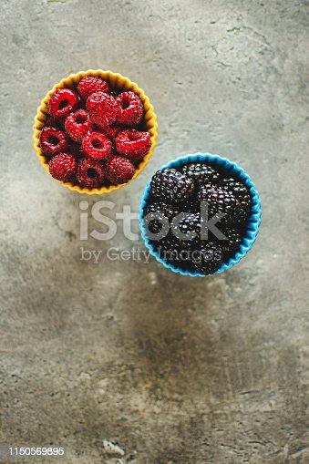 502634476istockphoto Blackberries and Raspberries in Ceramic Bowls on Rustic Stone Background 1150569895