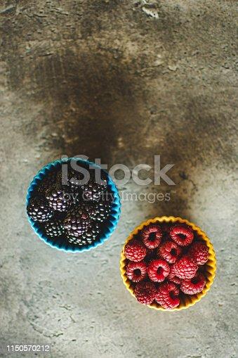 502634476istockphoto Blackberries and Raspberries in Ceramic Bowls on Rustic Stone Background 1150570212