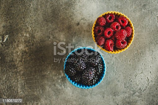 502634476istockphoto Blackberries and Raspberries in Ceramic Bowls on Rustic Stone Background 1150570272