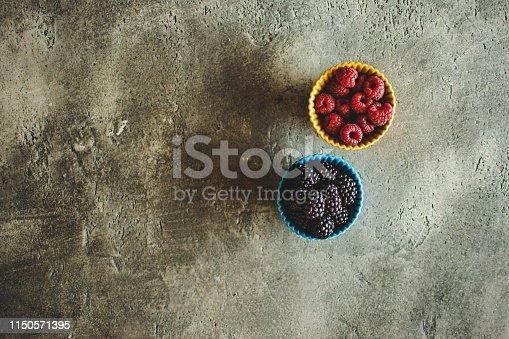 502634476istockphoto Blackberries and Raspberries in Ceramic Bowls on Rustic Stone Background 1150571395