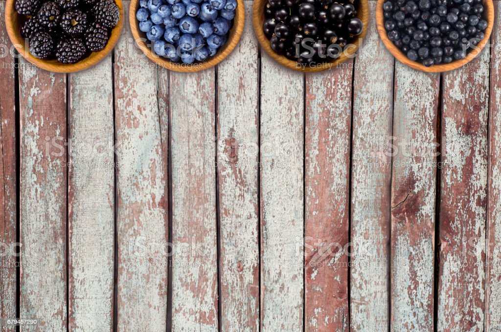 Blackberries, blueberries, currants and blueberries in a wooden bowls. royalty-free stock photo