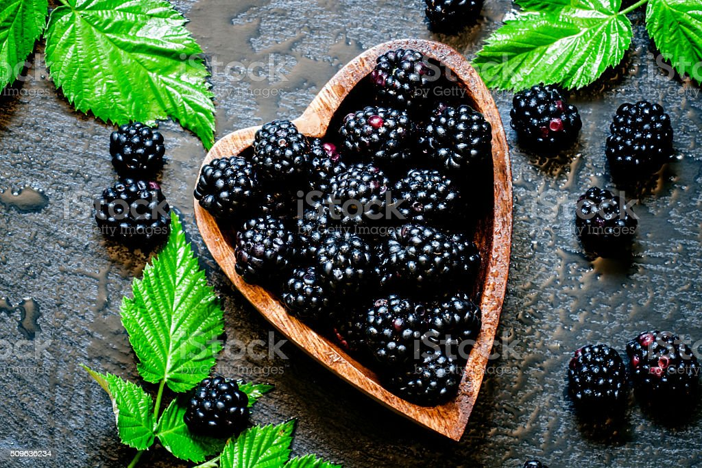 Blackberries in bowl in the shape of a heart stock photo