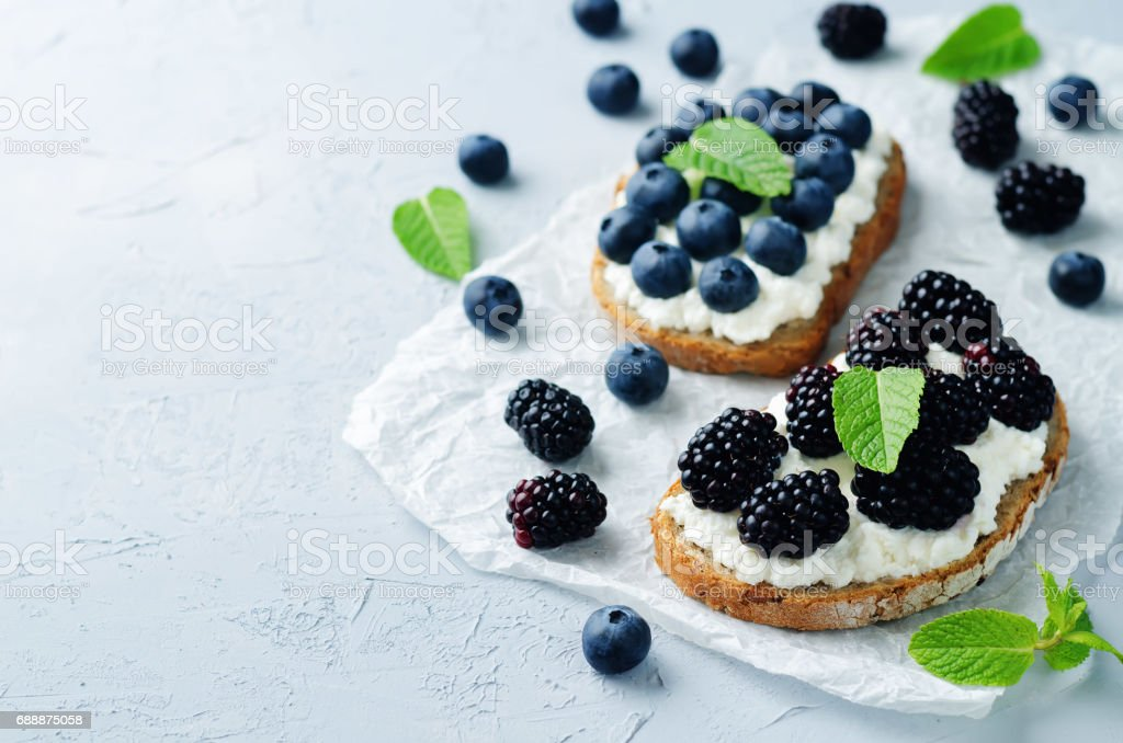 Blackberry and blueberry ricotta rye sandwiches stock photo