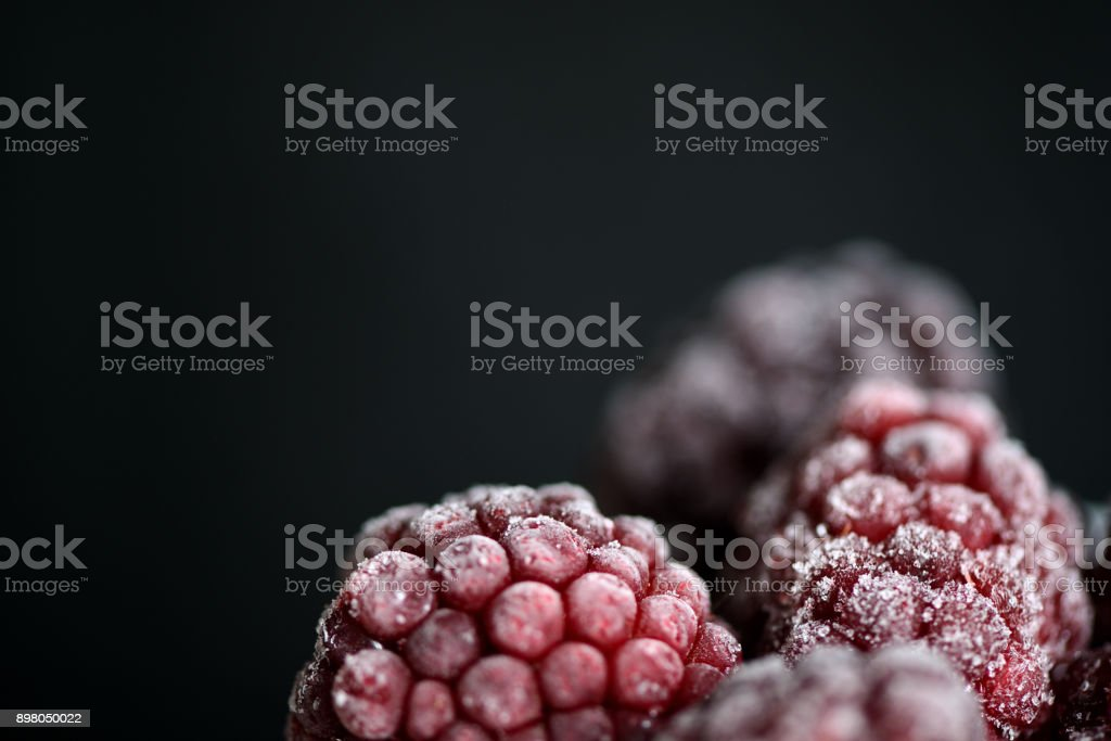 Blackberry berries covered with hoarfrost on a dark background close up stock photo