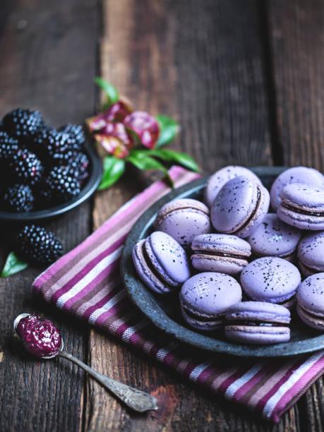 blackberry-makronen auf einem rustikalen holztisch. - desserts stock-fotos und bilder