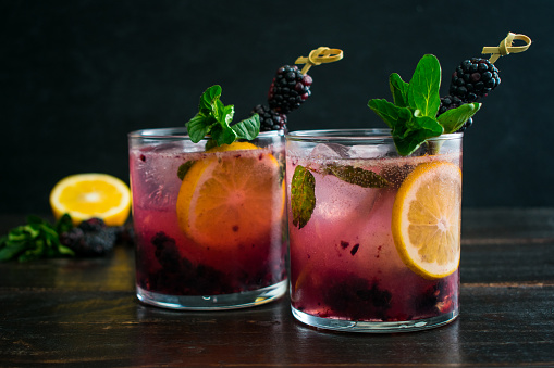 A sweet version of a gin and tonic cocktail made with fresh blackberries, mint, and Meyer lemon