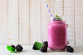 istock Blackberry smoothie in a mason jar with scattered berries over white wood 1130528629
