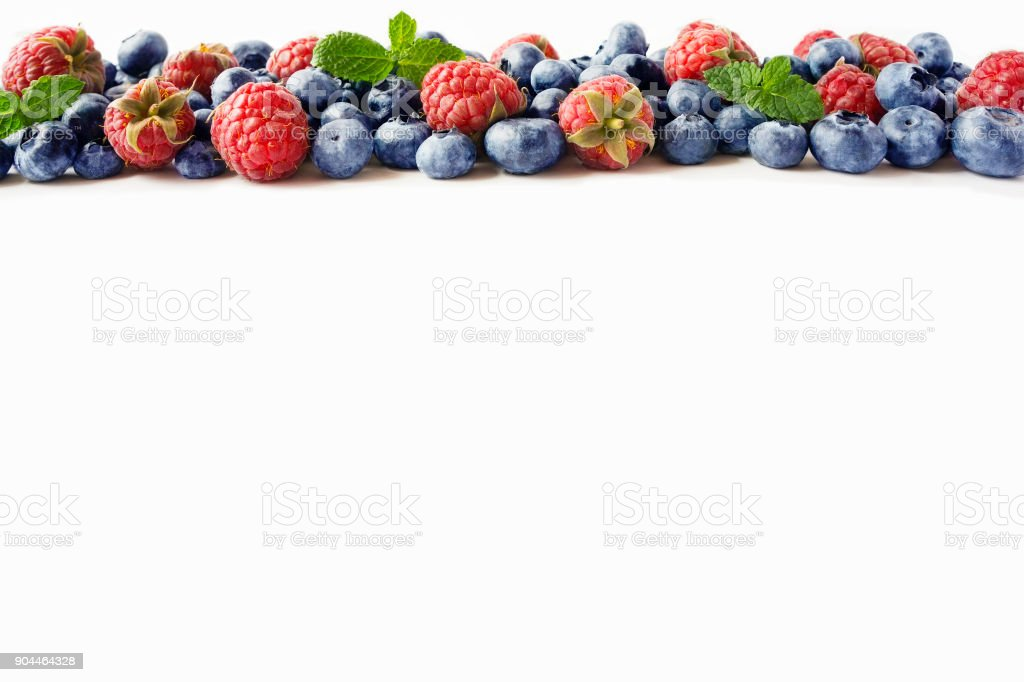 Black-blue and red berries. Ripe raspberries, blueberries with mint on white background. Berries at border of image with copy space for text. Background berries. Various fresh summer berries isolated on a white stock photo