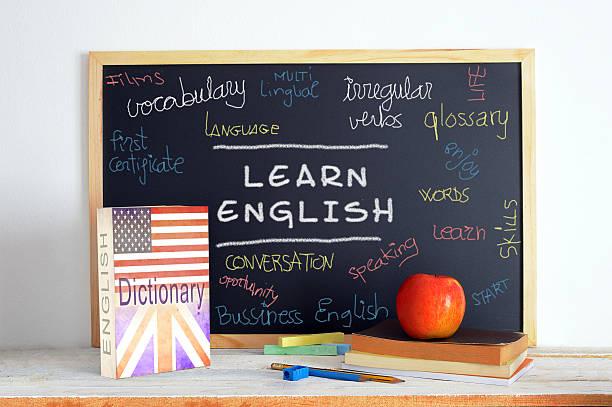 Pizarra y escuela material en una clase de inglés - foto de stock