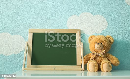 istock blackboard and toy on a background of clouds and sky 636932762