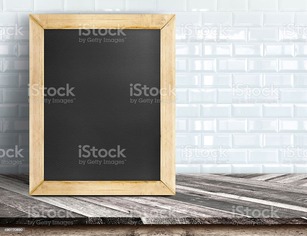 blackboard at white tiles wall and wood table stock photo