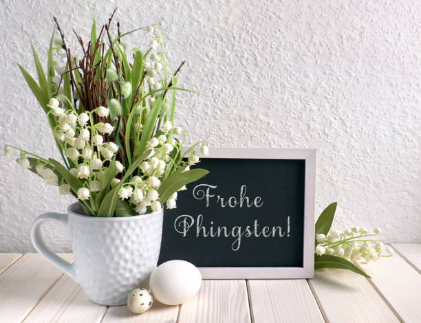 Blackboard decorated with lily of the valley flowers and eggs, text stock photo