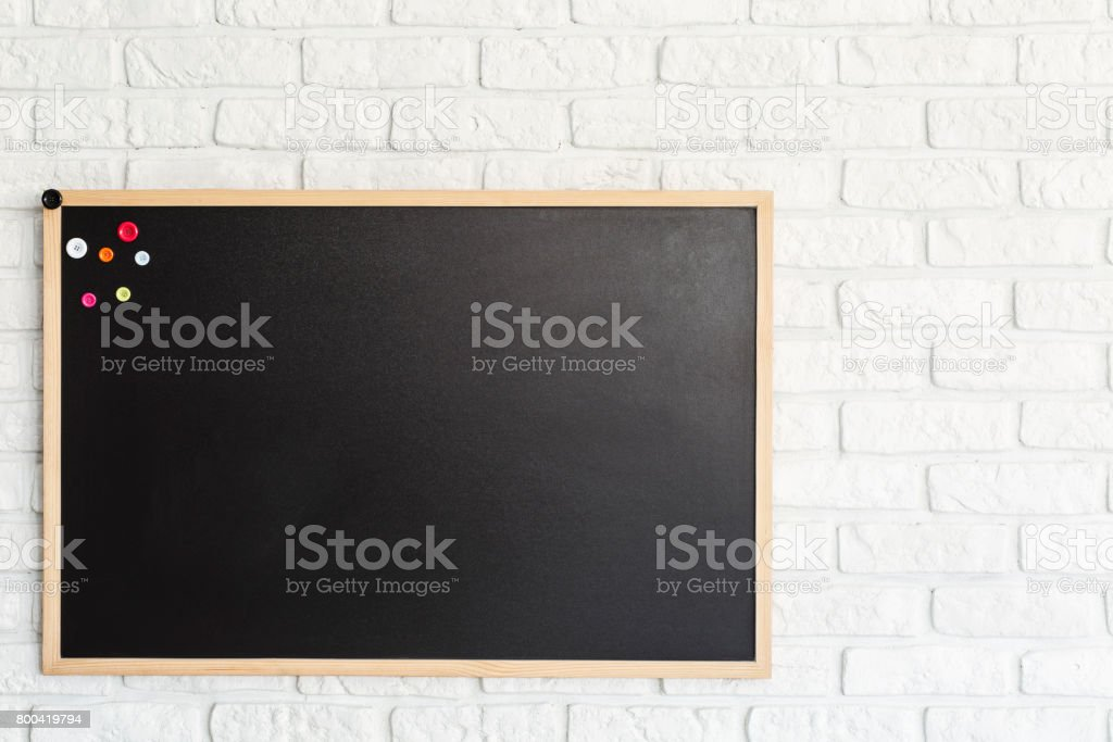 Blackboard hanging on brick wall stock photo