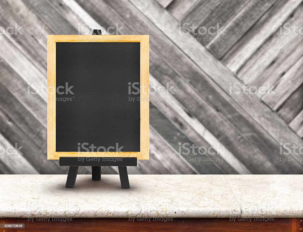 Blackboard menu with easel on marble table with blur wood stock photo