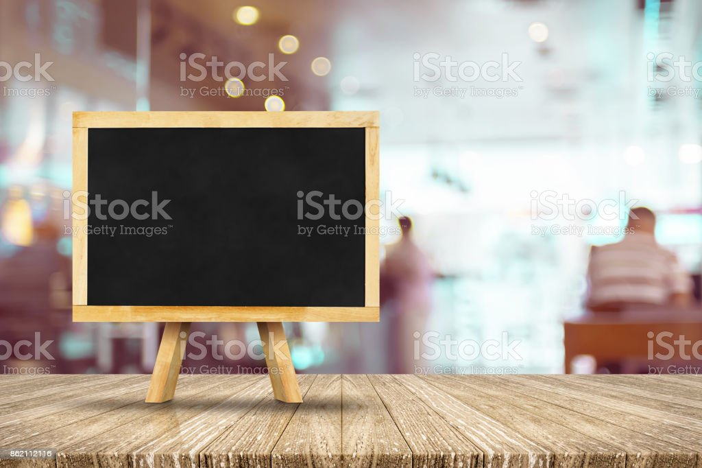 Blackboard menu with easel on wooden table with blur restaurant background, Copy space for adding your content stock photo
