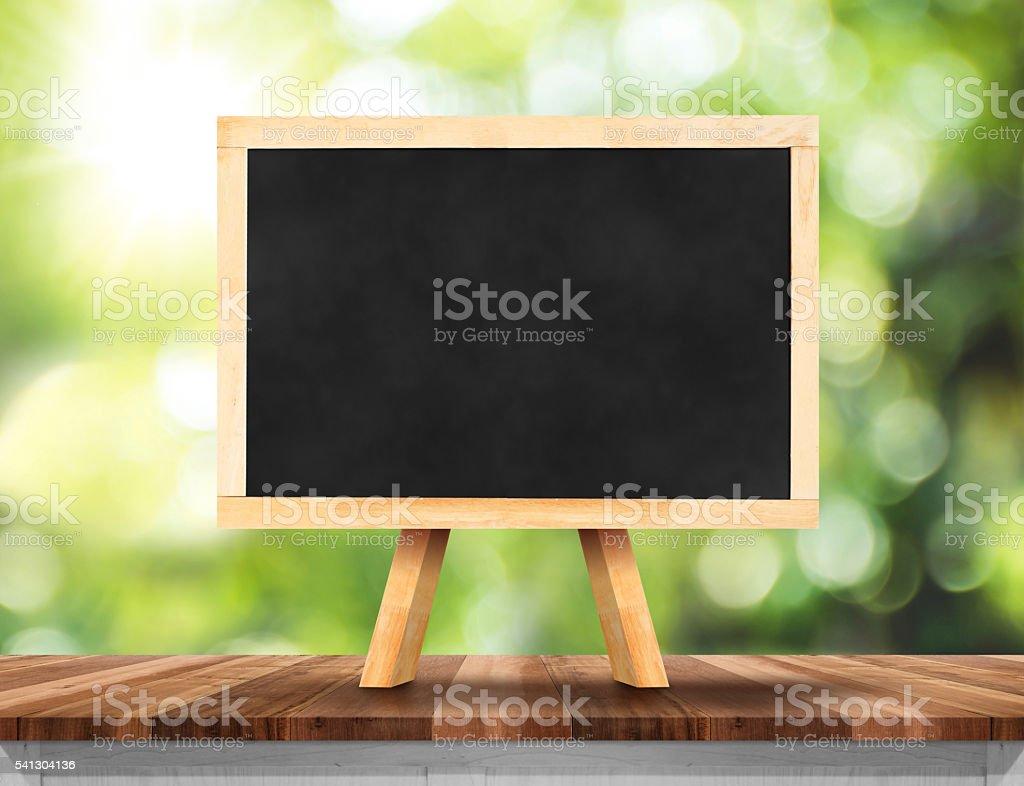 Blank blackboard on wood table with sun and blur green tree bokeh...