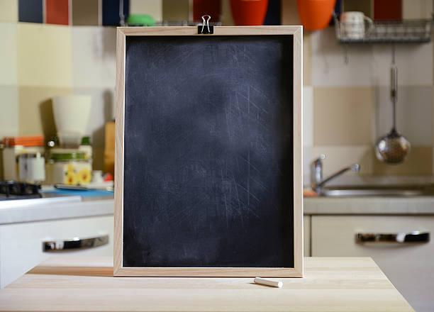 blackboard on wooden table on kitchen  background - kücheneinrichtung nostalgisch stock-fotos und bilder