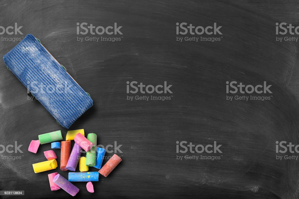 Blackboard with colorful broken chalks and board eraser, with copy...