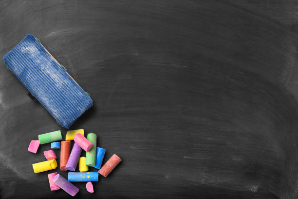 Blackboard with colorful broken chalks and board eraser stock photo