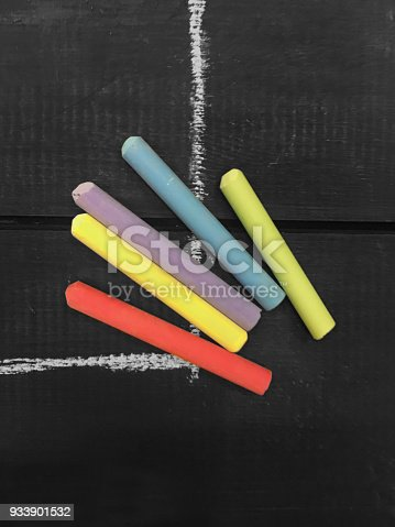 864458416istockphoto Blackboard with colorful chalk sticks 933901532