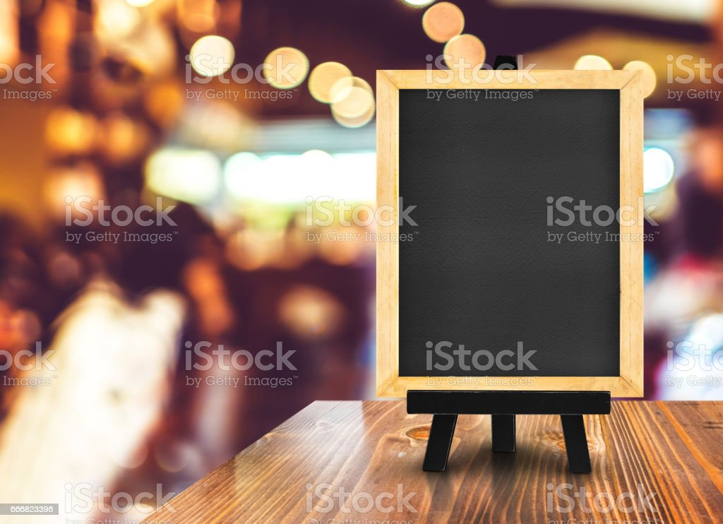 Blackboard with easel on wood table at blurred coffee shop background,Mock up for display or montage of design for online shopping promotion stock photo