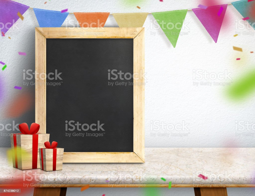 Blackboard with gift box and colorful flag banner on marble table at white wall,Leave space for display or montage of your design, Holiday new year concept stock photo