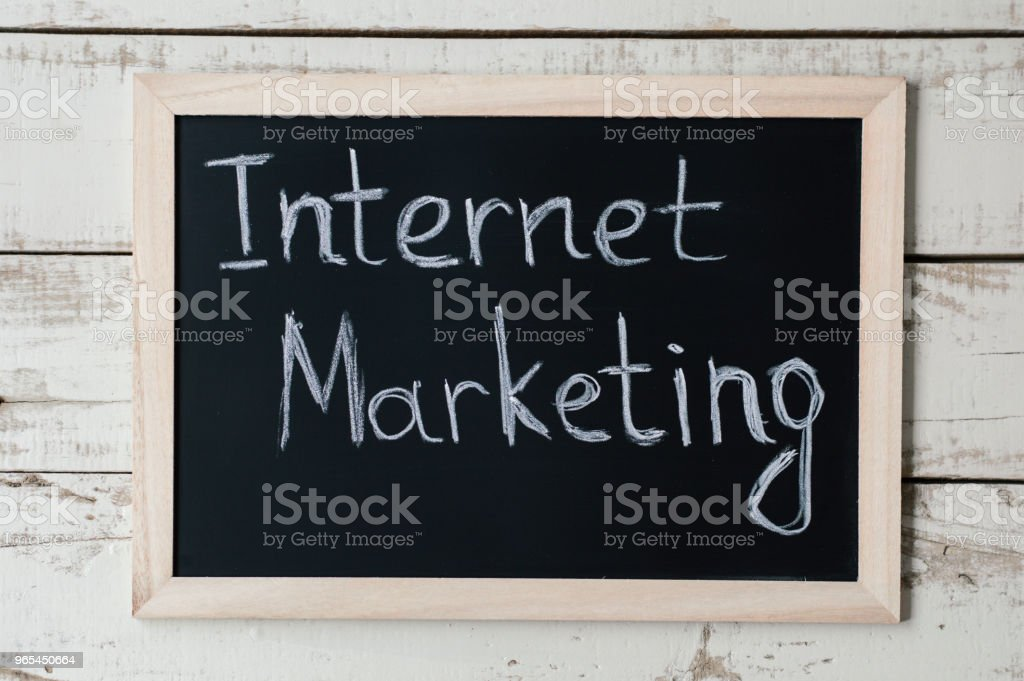 Blackboard with handwritten text 'Internet Marketing' on wooden background. Digital Marketing concept royalty-free stock photo