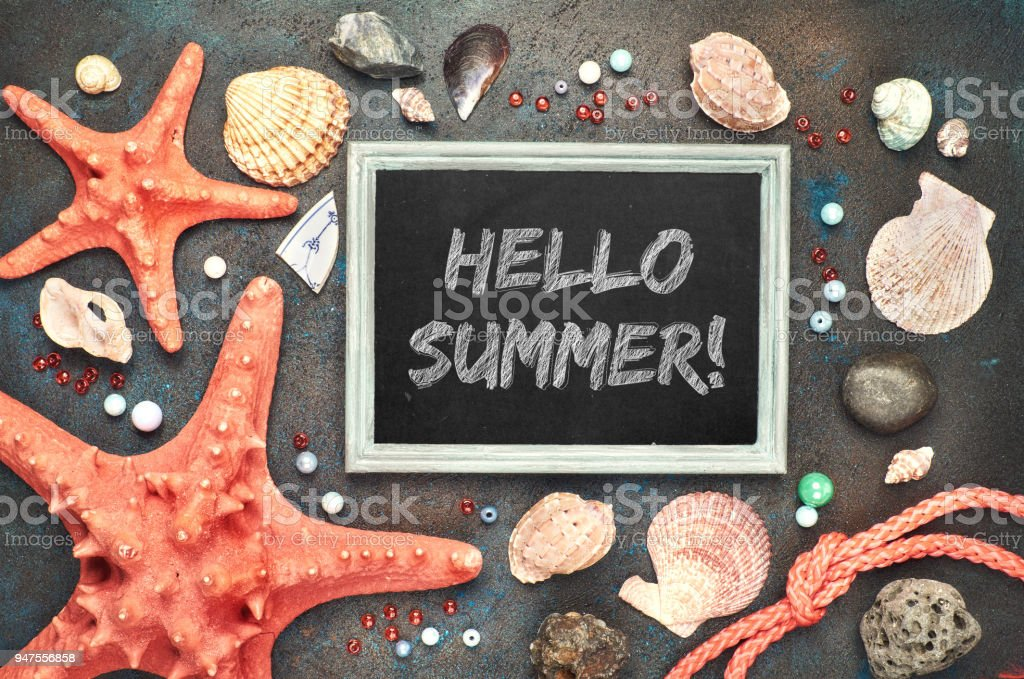 Blackboard with 'Hello Summer!' chalk text, with sea shells, rope and star fish on dark stock photo